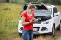 Portrait of young stressed woman standing at broken car and reading owner manual